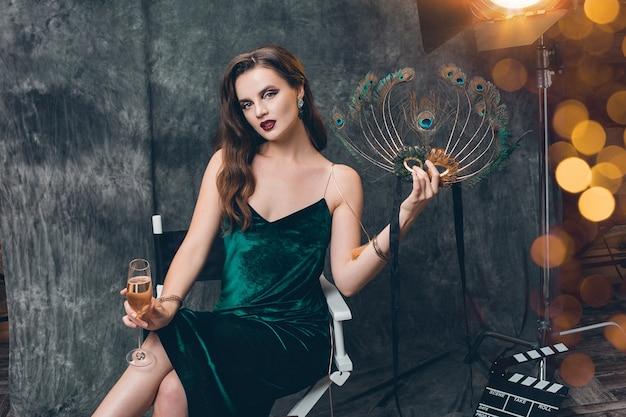 Jovem elegante mulher sexy sentada numa cadeira nos bastidores do cinema