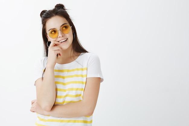 Jovem elegante posando com óculos de sol contra uma parede branca