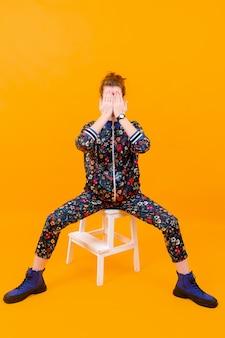 Jovem elegante posando em uma escada sobre fundo laranja