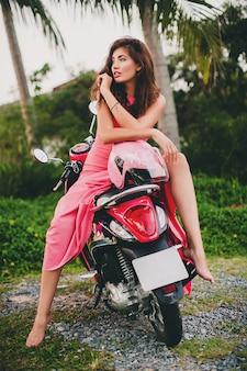 Jovem elegante sexy linda mulher com vestido rosa em scooter de moto
