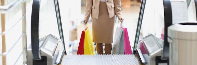 Jovem elegante sobe a escada rolante com sacolas de compras em um shopping center