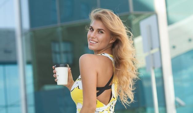 Jovem elegante tomando café para ir em uma rua da cidade