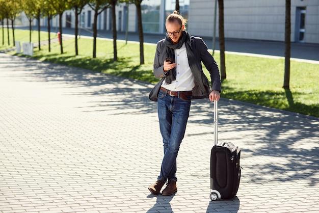 Jovem elegante usando seu smartphone em pé com mala perto de sair do aeroporto ao ar livre. estilo de negócios, viajante, estilo de vida moderno, viagem de negócios.