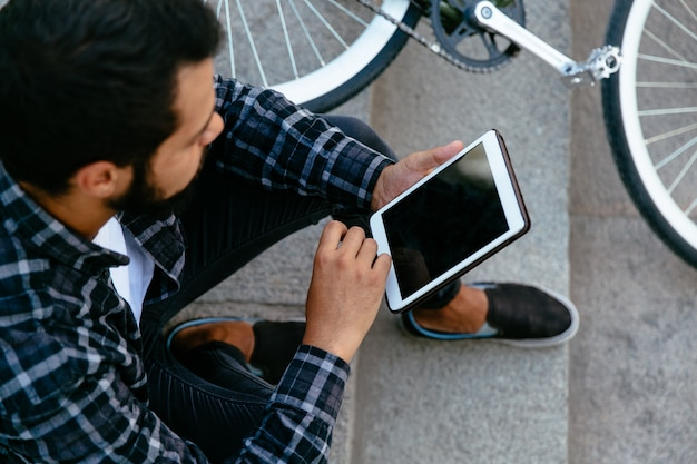 Jovem elegante usando um tablet, navegando em sites enquanto está sentado em etapas