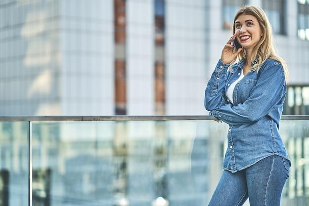 Jovem elegante vestindo roupas jeans e passando tempo ao ar livre