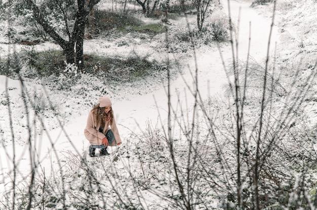 Jovem elegante vestindo roupas quentes, tocando a neve e aproveitando o fim de semana no inverno