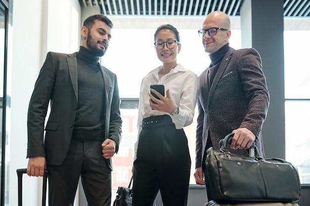 Jovem elegante viajante a negócios com smartphone e seus dois colegas do sexo masculino procurando o caminho certo para o hotel na rede