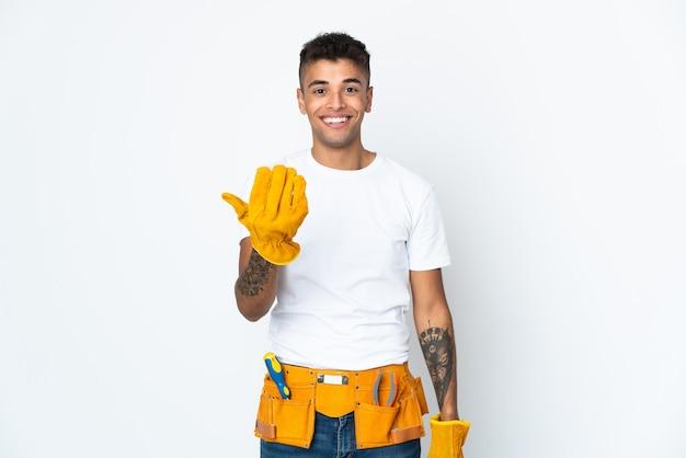 Jovem eletricista brasileiro manipulado em branco convidando a vir com a mão. feliz que você veio