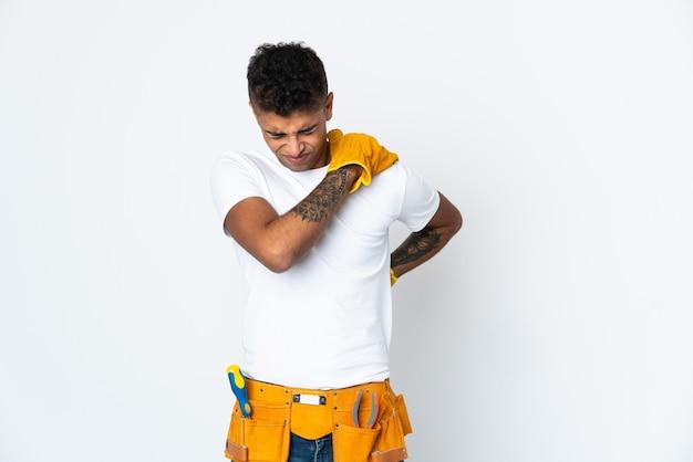Jovem eletricista brasileiro manipulado isolado em parede branca sofrendo de dores no ombro por ter feito esforço