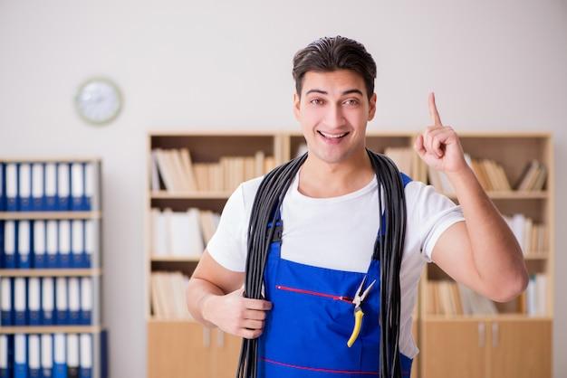 Jovem eletricista com cabo trabalhando no escritório