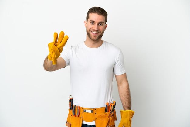 Jovem eletricista em uma parede branca isolada feliz e contando três com os dedos