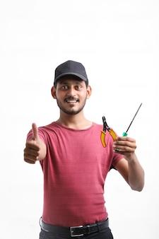 Jovem eletricista indiano segurando ferramentas na mão e em pé sobre um fundo branco.