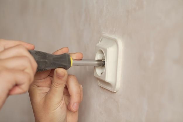 Jovem eletricista instalando tomada elétrica na parede com chave de fenda