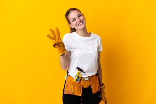 Jovem eletricista isolada na parede amarela feliz e contando três com os dedos