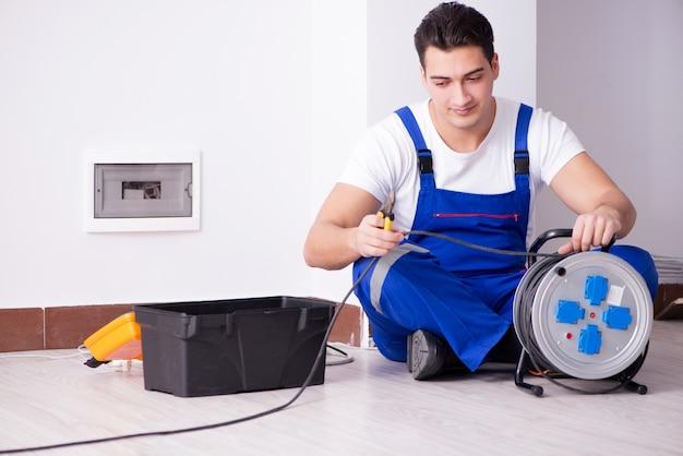 Jovem eletricista trabalhando no soquete em casa