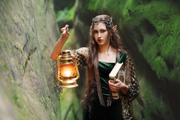 Jovem elfo feminino linda andando pela floresta com um boo