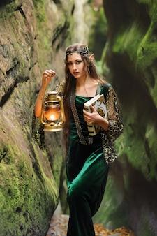 Jovem elfo feminino lindo andando pela floresta com um livro e uma lanterna