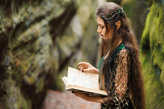 Jovem elfo feminino vagando na floresta segurando um livro antigo