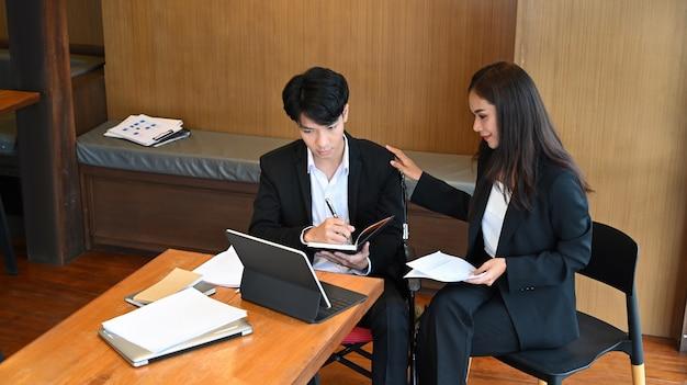 Jovem em cadeira de rodas, trabalhando com seu colega no escritório.