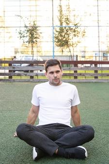 Jovem em camisa branca em campo de futebol artificial