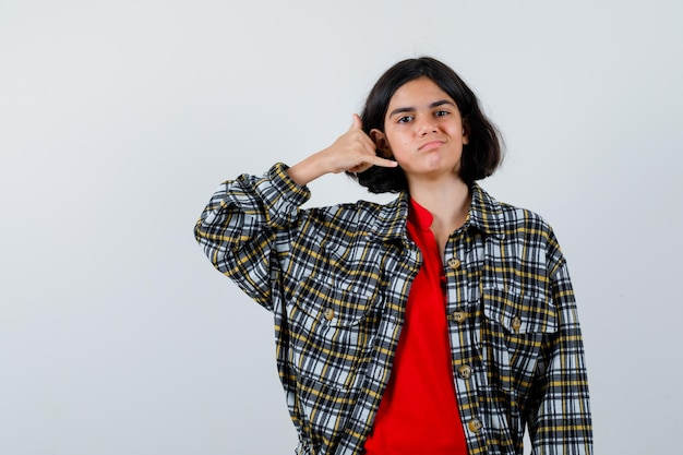 Jovem em camisa e t-shirt vermelha mostrando me chama de gesto e olhando sério, vista frontal.