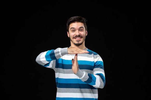 Jovem em camisa listrada de azul com gesto de mão para pausa