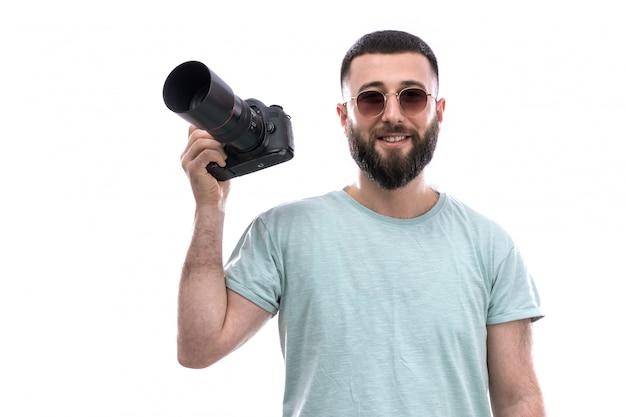 Jovem em camiseta azul com barba e óculos de sol, segurando a câmera fotográfica