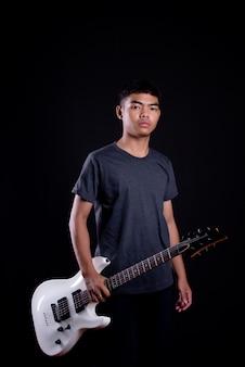 Jovem em camiseta escura com guitarra elétrica