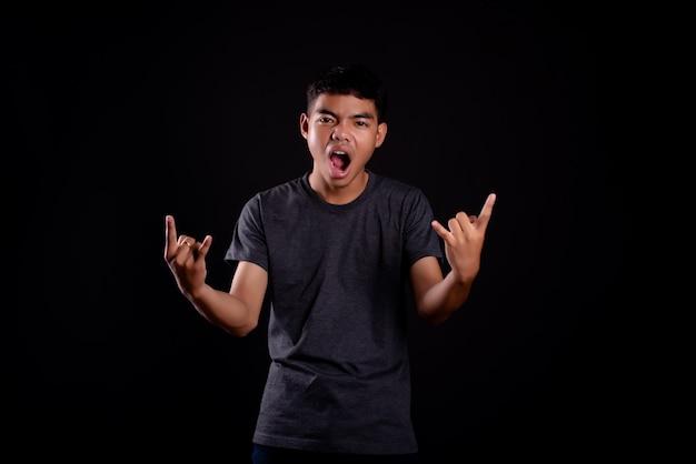 Jovem em camiseta escura, fazendo um gesto de roqueiro