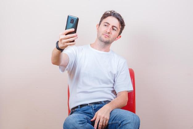 Jovem em camiseta, jeans tirando uma selfie no celular enquanto está sentado na cadeira