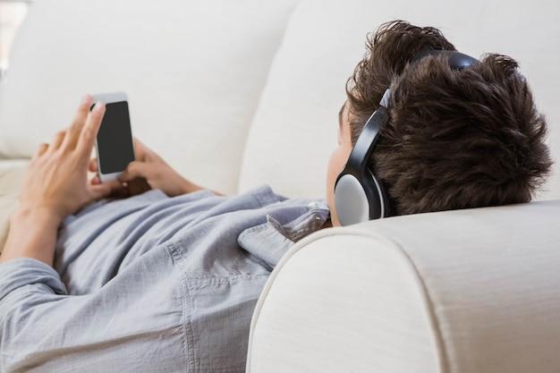 Jovem em casa relaxando no sofá ouvindo música no celular