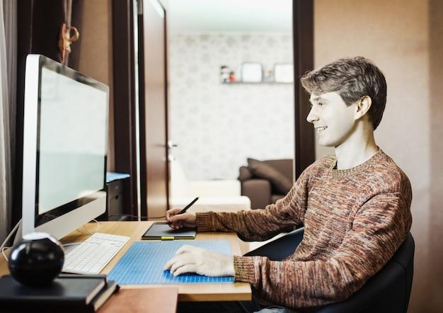Jovem em casa usando um computador, desenvolvedor autônomo ou designer trabalhando em casa.