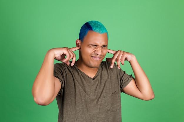 Jovem em casual na parede verde tapando as orelhas com os dedos