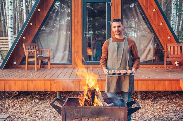 Jovem em dia quente de outono churrasco ao ar livre
