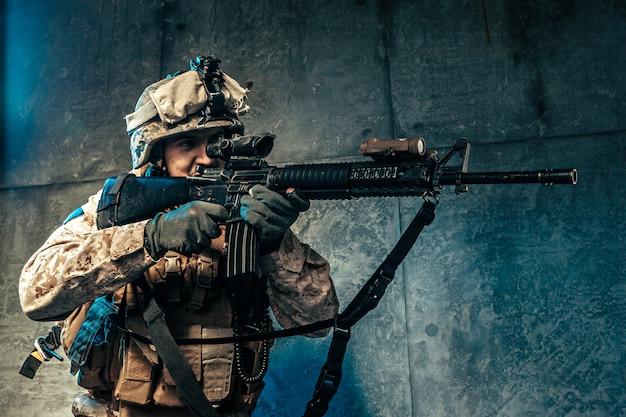 Jovem em equipamento militar, um soldado mercenário nos tempos modernos em um escuro no estúdio