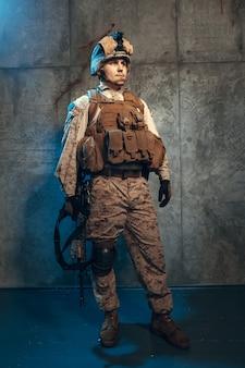Jovem em equipamento militar, um soldado mercenário nos tempos modernos no escuro