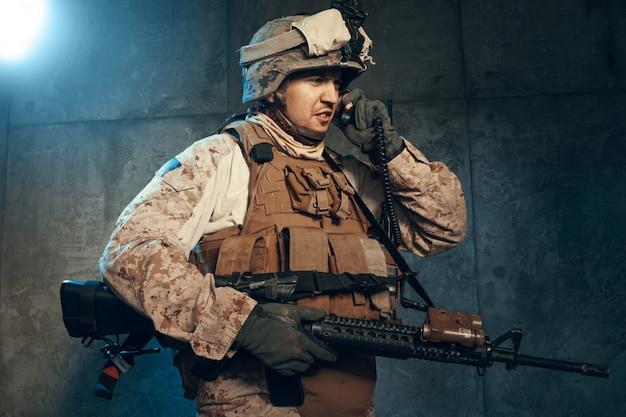Jovem em equipamento militar, um soldado mercenário nos tempos modernos, sobre um fundo escuro no estúdio