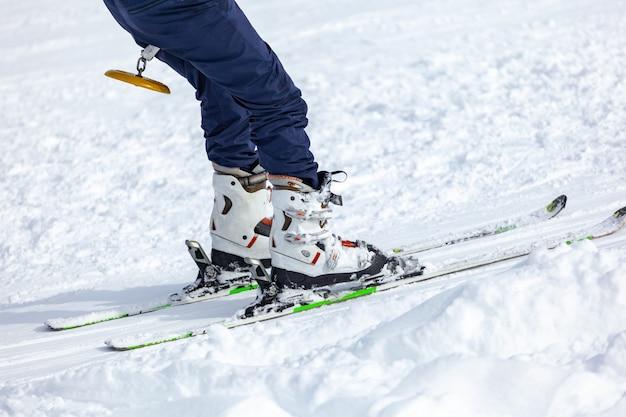 Jovem em esquis fora de encostas, equipamentos e esportes radicais de inverno em local para esquiar