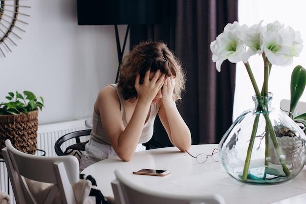 Jovem em estado de choque sentada à mesa da sala. adolescente chorando