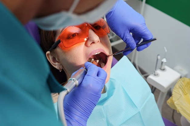 Jovem em exame preventivo na cadeira odontológica do dentista. conceito de cuidados com os dentes.