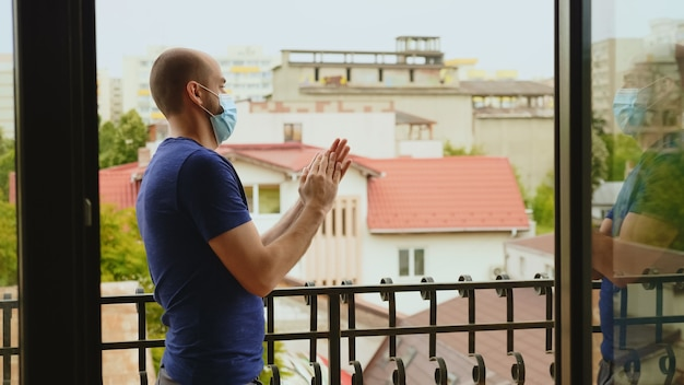 Jovem em êxtase com máscara de proteção na varanda aplaudindo em apoio ao pessoal médico na luta contra covid-19. Foto Premium