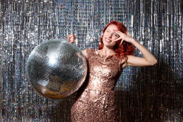 Jovem em festa com bola de discoteca em cortinas brilhantes