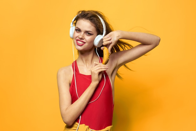 Jovem em fones de ouvido se divertindo e rindo, festa de maiô, parede amarela