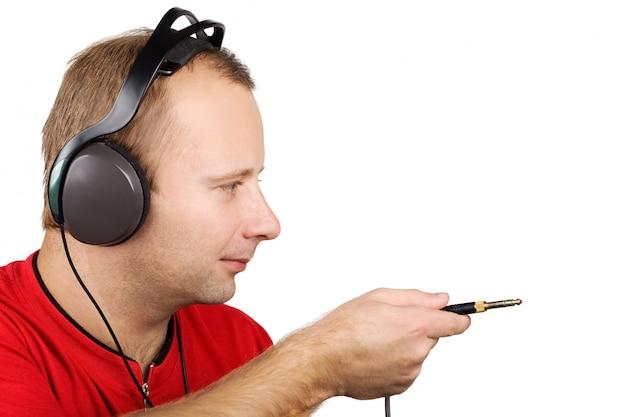 Jovem em fones de ouvido segurando jack plug na mão