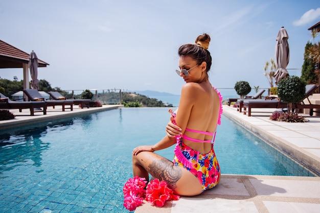 Jovem em forma de mulher bronzeada e tatuada em um maiô de flor rosa bem na moda, aberta na beira da piscina