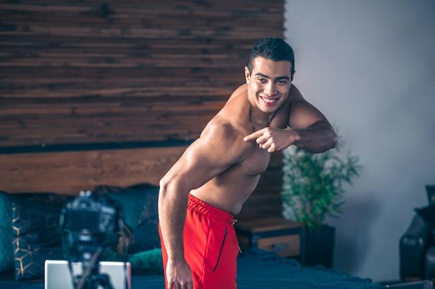 Jovem em forma de vlogger esportivo de short vermelho demonstrando seus bíceps