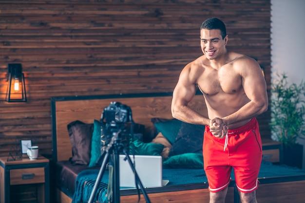 Jovem em forma de vlogger esportivo de short vermelho demonstrando seus músculos para a câmera