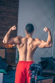 Jovem em forma de vlogger esportivo de short vermelho demonstrando suas costas fortes