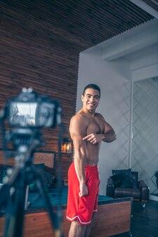 Jovem em forma de vlogger esportivo em shorts vermelhos mostrando seus tríceps