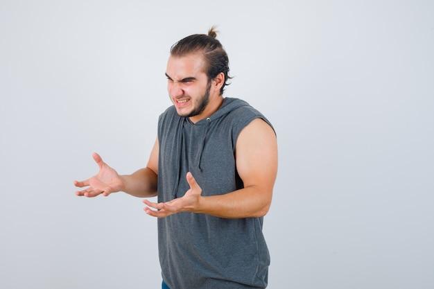 Jovem em forma masculina em um moletom sem mangas, mantendo as mãos de maneira agressiva e parecendo rancoroso, de frente.